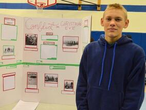 Student standing next to his History Fair project